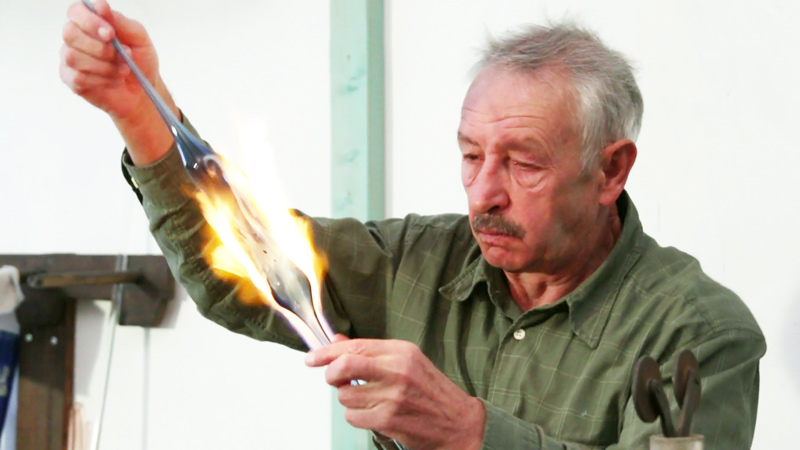 Man aan glasblazen in het glasmuseum
